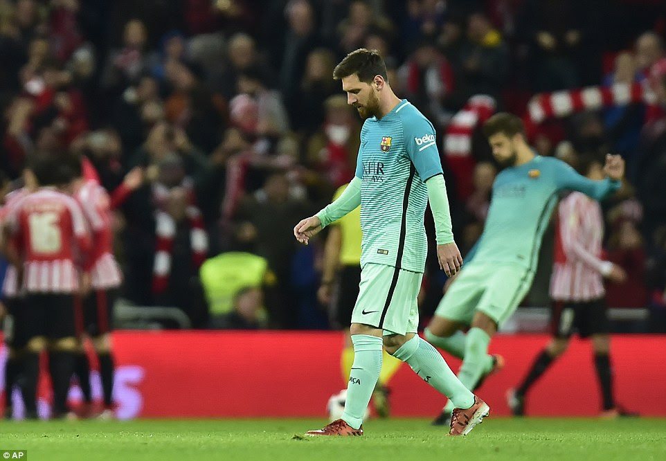 Lionel Messi cuts a dejected figure as Athletic players celebrate, while Gerard Pique kicks the ball back to the centre circle