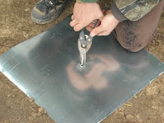 Cutting Out the Drilled Center Hole in the Flashing for the Concrete Pier Homemade Termite Shield