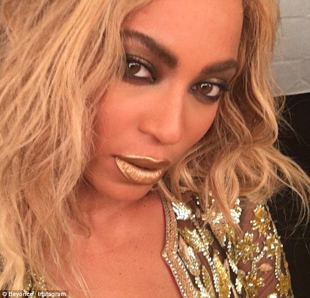 Golden girl: Bey wears gold lipstick and smolders at the camera in another selfie she shared