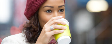 Young woman drinking takeout coffee (Thinkstock)