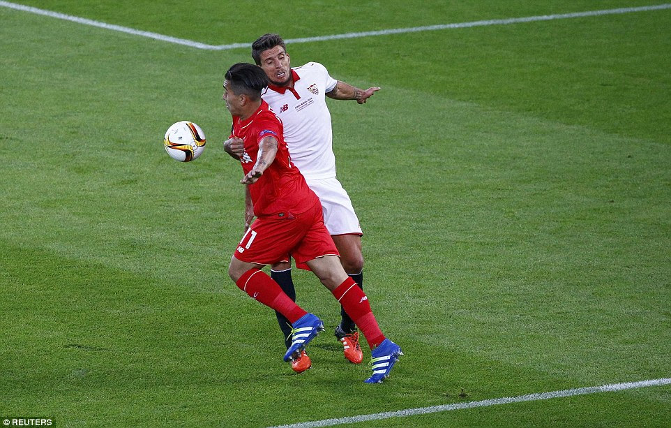 Sevilla's Caricco (right) appears to handle the ball as Liverpool forward Firmino bursts into the box during the first half