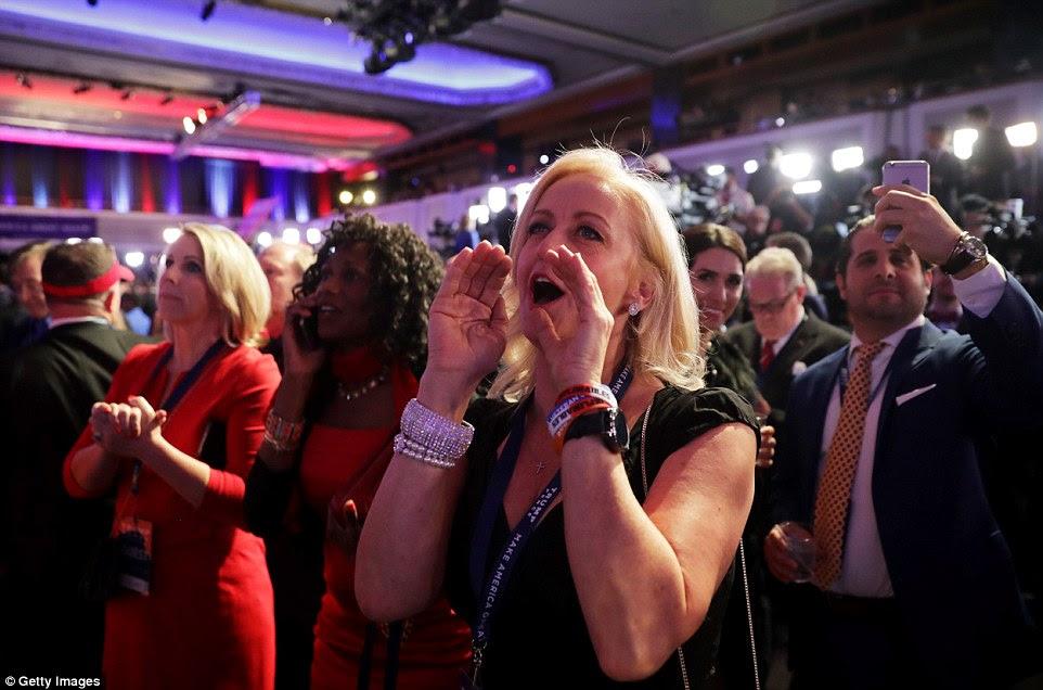 Delight: Uma mulher na reunião da eleição de Trump em aplausos Nova York como resultados eleitorais são mostrados aos partidários do candidato republicano