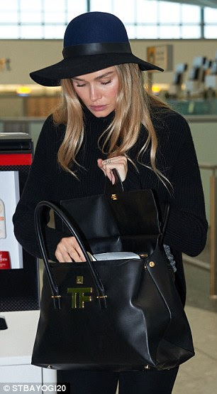 Fashionable flyer: Renée sported a black knit top and large fedora as she lugged around a large black leather Tom Ford bag