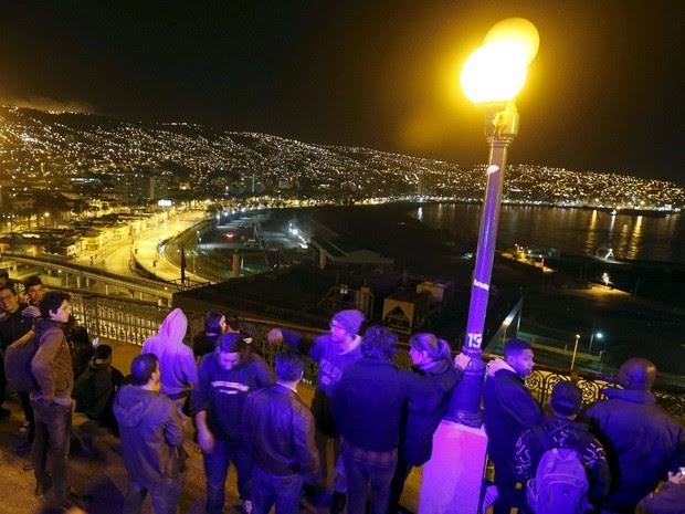 Pessoas olham o mar em Valparaíso, no litoral do Chile após alerta de tsunami (Foto: Rodrigo Garrido/AFP)