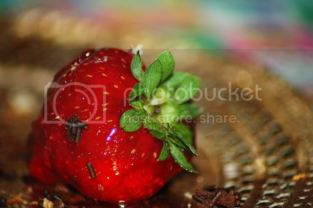 A detail of a strawberry on a cardboard platter [enlarge]