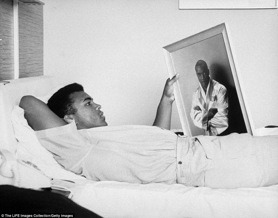 A candid snap of the legendary boxer shows him looking at a picture of fellow boxer Liston, who he was training to fight in 1964