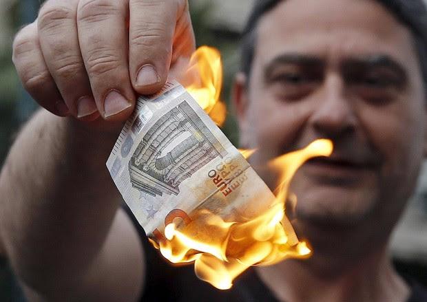 Manifestante anti-austeridade queima uma nota de Euro em frente aos escritórios da União Europeia em Atenas neste domingo  (Foto: Reuters/Alkis Konstantinidis)