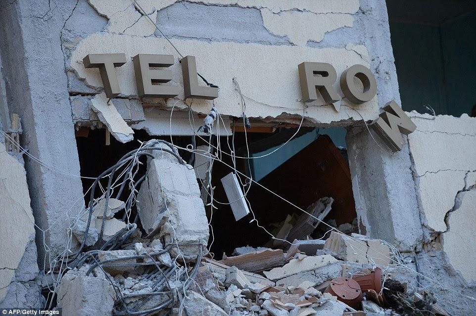 Nada deixado: Sinal deste loja está pendurado e suas paredes são recolhidos após o tremor sacudiu a área em torno de 03:30