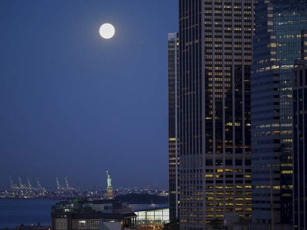 Lua azul, chamada assim por ser a segunda lua cheia do mês, é vista perto da Estátua de Liberdade, em Nova York, nesta sexta-feira (31) (Foto: REUTERS/Eduardo Munoz)