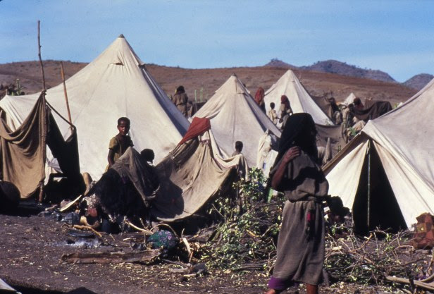 Ethiopian famine victims stand at their tents at the refugee camp camp in Bati.