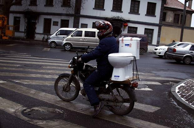 Motocista é flagrado levando privada na moto. (Foto: David Gray/Reuters)