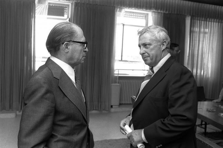 Israeli Prime Minister Menahem Begin speaks with Israeli Agriculture Minister Ariel Sharon (R) in the Prime Minister's office in Jerusalem August 9, 1977 in this file photo released by the Government Press Office. Surgeons battled to keep Sharon alive on January 5, 2006 after a massive brain haemorrhage felled the Israeli prime minister in the midst of his fight for re-election on a promise to end conflict with the Palestinians. Reuters