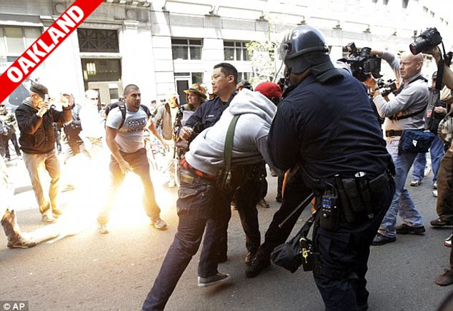 Confrontation: Demonstrators clash with police as a tear gas canister goes off in the background during May Day protests in Oakland