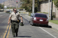 A police official carries a helmet as he walks past the Maplewood Apartments after a shooting in Lakeside, Calif., Tuesday, Sept. 25, 2012. The San Diego County sheriff's Capt. Duncan Fraser said two deputies and a suspect have been shot while the deputies were trying to contact a child abuse suspect at the suburban apartment complex. (AP Photo/Gregory Bull)