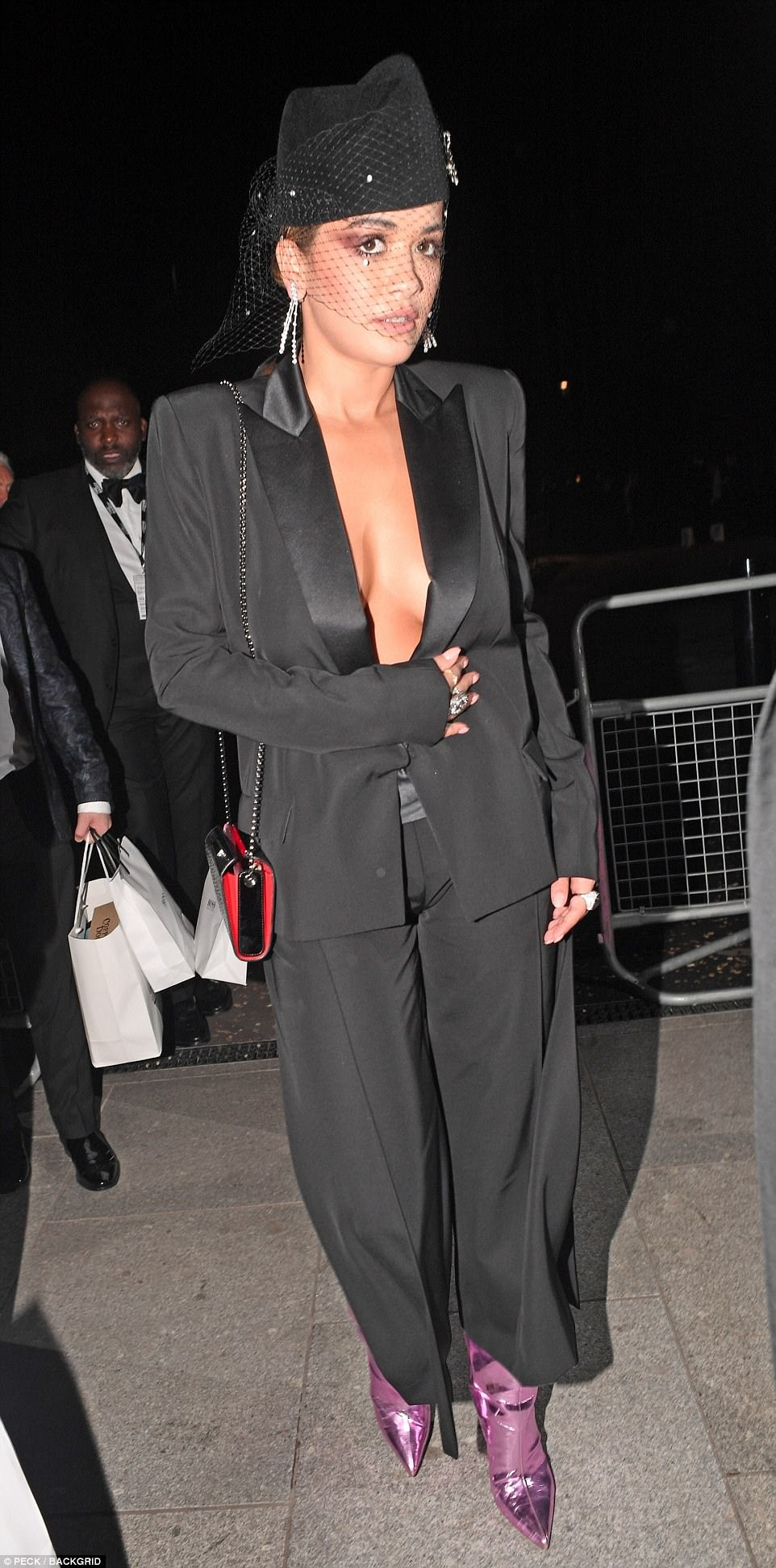 Hot right now!Rita Ora brought some sensational sex appeal to the red carpet as she went braless beneath a suit jacket it a tuxedo-inspired ensemble with pink metallic boots