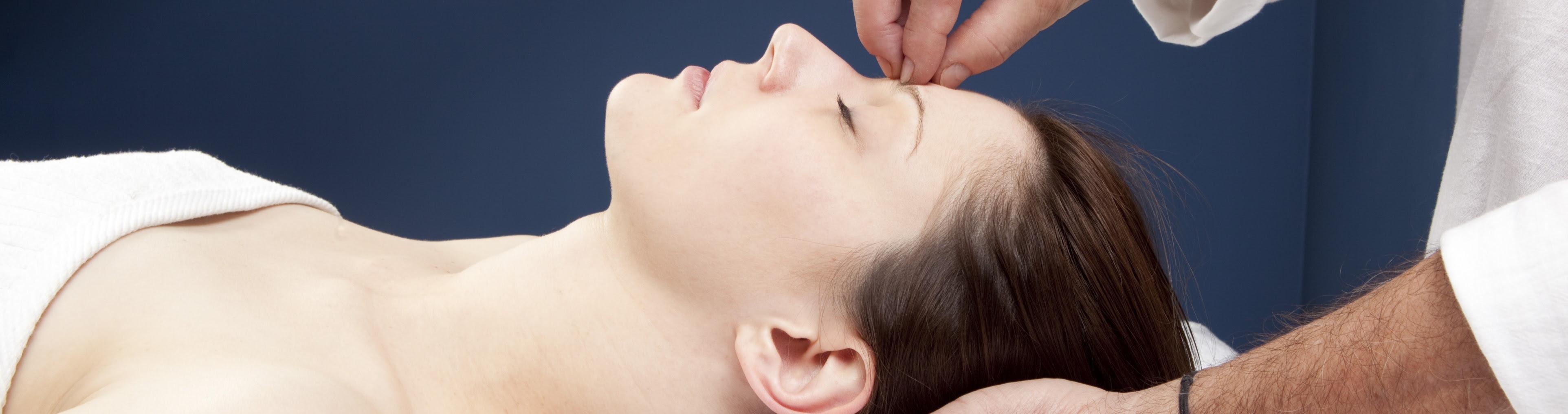 FOTO: Mulher deitada, com os olhos fechados, demonstrando relaxamento, e os dedos do terapeuta na testa da mulher, como quem induz o relaxamento hipnótico