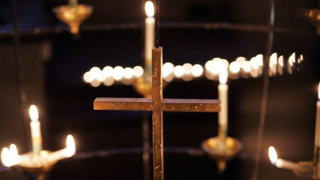 A cross and lit candles