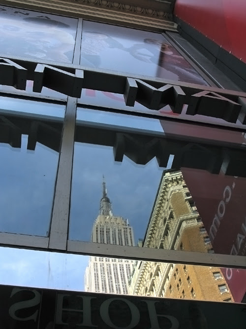 the Empire State Building reflects in 6th Avenue windows of the Manhattan Mall, NYC