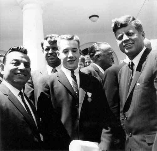 President John F. Kennedy, circa 1962. In the background are Robert F. Kennedy and J. Edgar Hoover, director of the FBI.