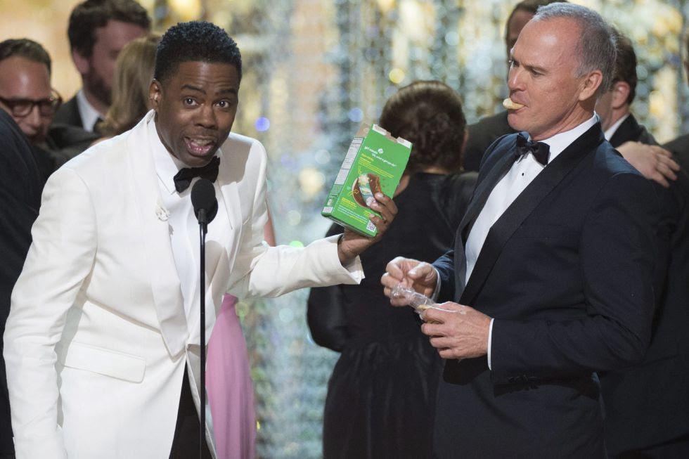 Chris Rock despide la gala mientras le observa comiendo galletas Michael Keaton, del reparto de 'Spotlight'