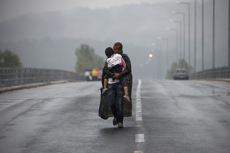 Syrian refugee kisses his daughter as he walks through a rainstorm towards Greece's border with Macedonia, near the Greek village of Idomeni (Yannis Behrakis, Thomson Reuters  - September 10, 2015).