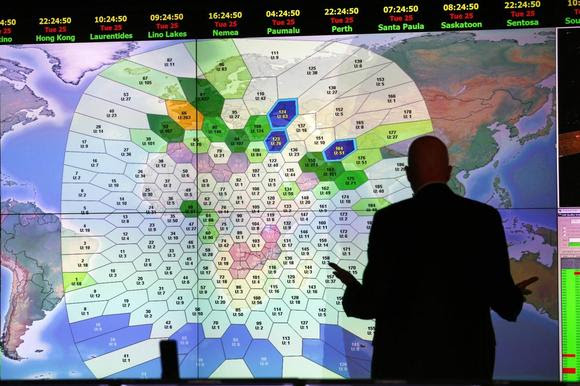 A member of staff at satellite communications company Inmarsat works in front of a screen showing subscribers using their service throughout the world, at their headquarters in London March 25, 2014. REUTERS/Andrew Winning