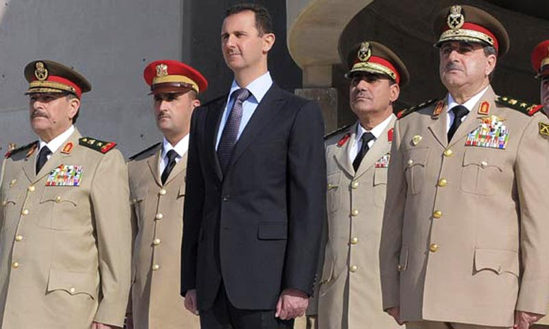 In this Thursday, Oct 26, 2011 file photo, Syrian President Bashar Assad, center, stands next to Syrian Defense Minister Gen. Dawoud Rajha, right, and Chief of Staff Gen. Fahed al-Jasem el-Freij, left, during a ceremony to mark the 38th anniversary of the October 1973 Arab-Israeli war, in Damascus, Syria. -AP File Photo