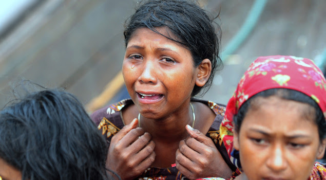 An emotional Rohingya Muslim woman, fleeing sectarian violence in Myanmar, is pictured on an intercepted boat trying to cross the Naf river into Bangladesh in Teknaf on June 13, 2012.