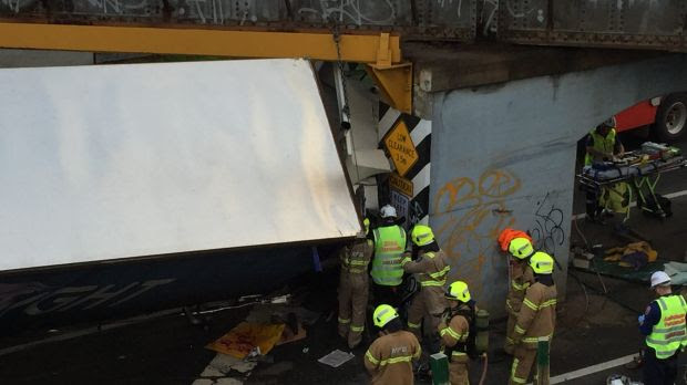 Fire crews frantically try to free the trapped truck driver.