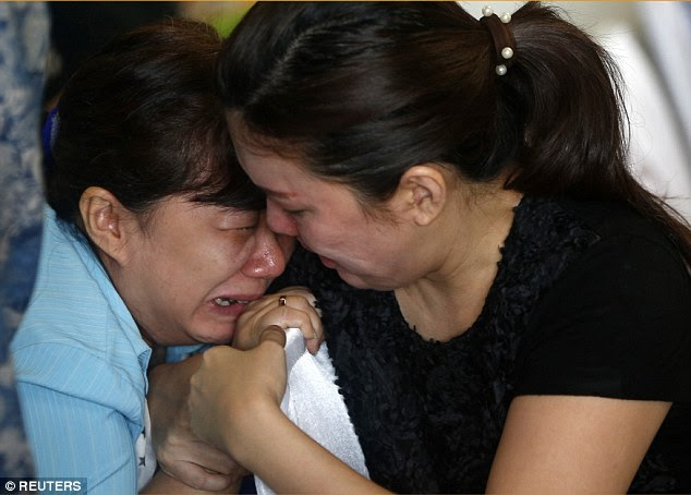 Inconsolable: Family members of passengers on board missing AirAsia flight QZ8501 cry at a waiting area in Juanda International Airport as they wait for news of the search and rescue operation