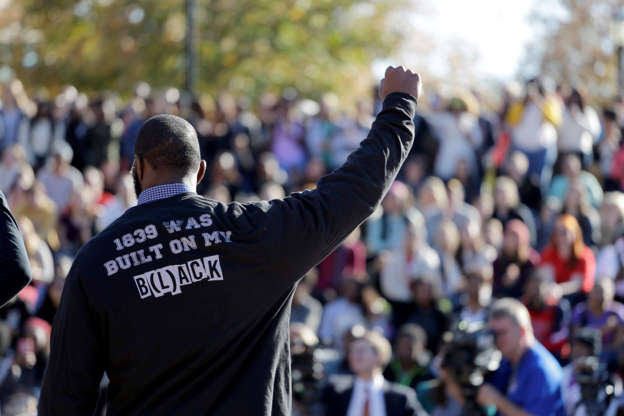 A member of the black student protest group Concerned Student 1950 gestures on Monday while addressing a crowd following the announcement that University of Missouri System President Tim Wolfe would resign, at the university in Columbia, Mo.