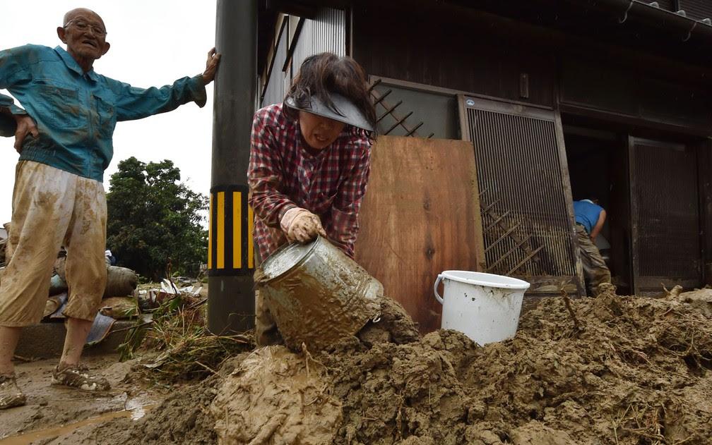 Moradores tiram lama de suas casas após enchente em Asakura, em Fukuoka, no Japão, na quinta (6) (Foto: Kazuhiro Nogi/AFP)