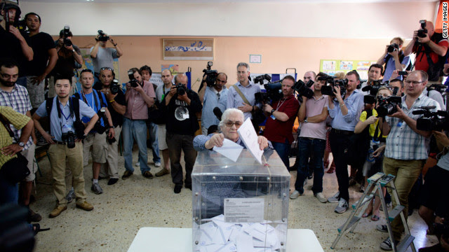 A woman, surrounded by media, casts her vote at a polling station in Athens, Greece, Sunday, June 17.