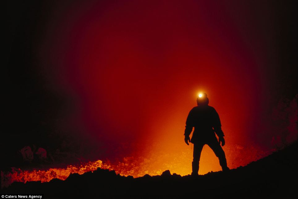A geologist silhouetted by glowing lava at Mount Etna. The molten rocks hit over 2000 degrees Farenheit (1100 degrees Celsius) and were studied by the geology scientists during an expedition to live volcanoes