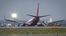 El Boeing 737 de Southwest Airlines se encuentra posado en la pista del aeropuerto de LaGuardia, después de hacer un aterrizaje de emergencia sin su tren de aterrizaje.