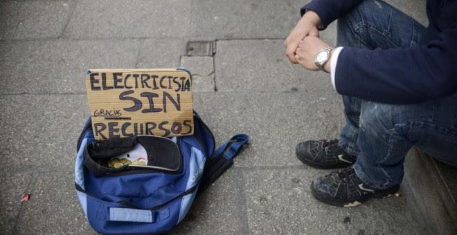 Un hombre en situación de pobreza pide en la calle.- EFE