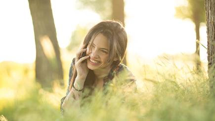 A woman in a sunshine-dappled sylvan scene laughs and uses her mobile phone