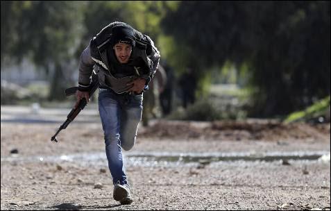 Un combatiente del Ejército sirio libre corre buscando refugio, en un suburbio de Damasco.