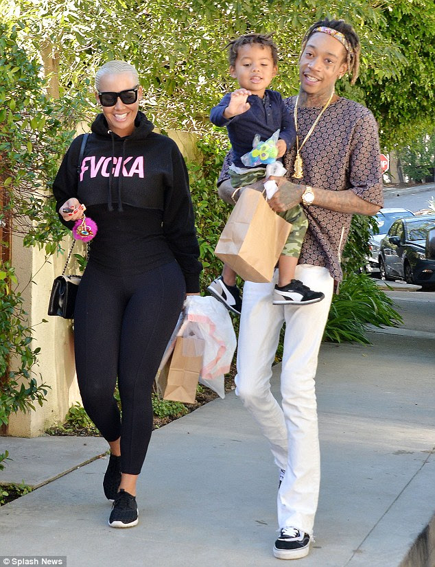 Making it personal: Amber's conversation came in the wake of the epic twitter tirade between Kanye and Wiz - which referenced the former strippers two-year-old son Sebastian - she is seen here with Wiz and their boy in LA