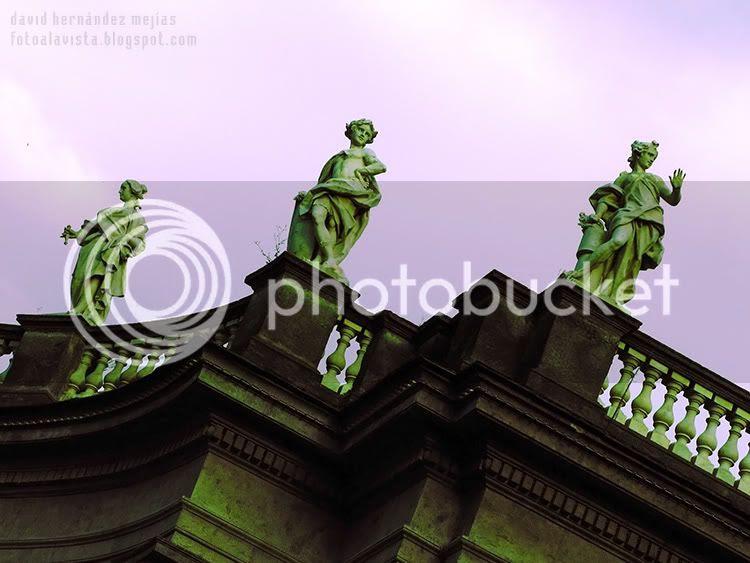 Contrapicado hacia el cielo con balaustrada y 3 esculturas en un edificio de Nápoles, Italia