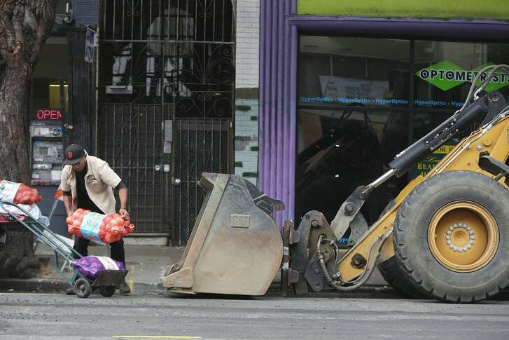 Sam Afuhaamango of Manu Produce picks up a bag of produce that had tipped over as he loads a dolly with produce next to construction equipment not being used during a delivery on Haight Street between Masonic and Ashbury on Friday, October 23,  2015 in San Francisco, Calif.
