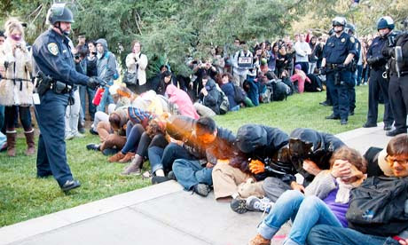 A police officer pepper-sprays students at an Occupy protest at University of California, Davis