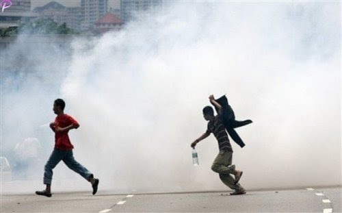 Protesters run away from tear gas fired by Malaysian riot police during a protest against the use of English to teach math and science in Kuala Lumpur, Malaysia, Saturday, March 7, 2009. AP Photo