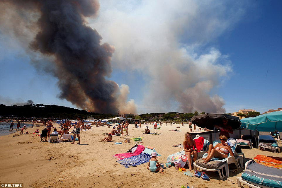 Smoke fills the sky above a burning hillside as tourists relax on the beach in Bormes-les-Mimosas, France, on July 26 as wildfires spread through the country. More than 10,000 residents and holidaymakers were forced to flee the flames and actress Joan Collins was forced to abandon her home near Saint Tropez