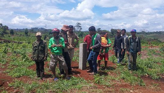 Ethnic Bunong villagers in Mondulkiri's Pichreada district stand next to demarcation post yesterday that they claim was recently placed by KPIS Investment company. Photo supplied
