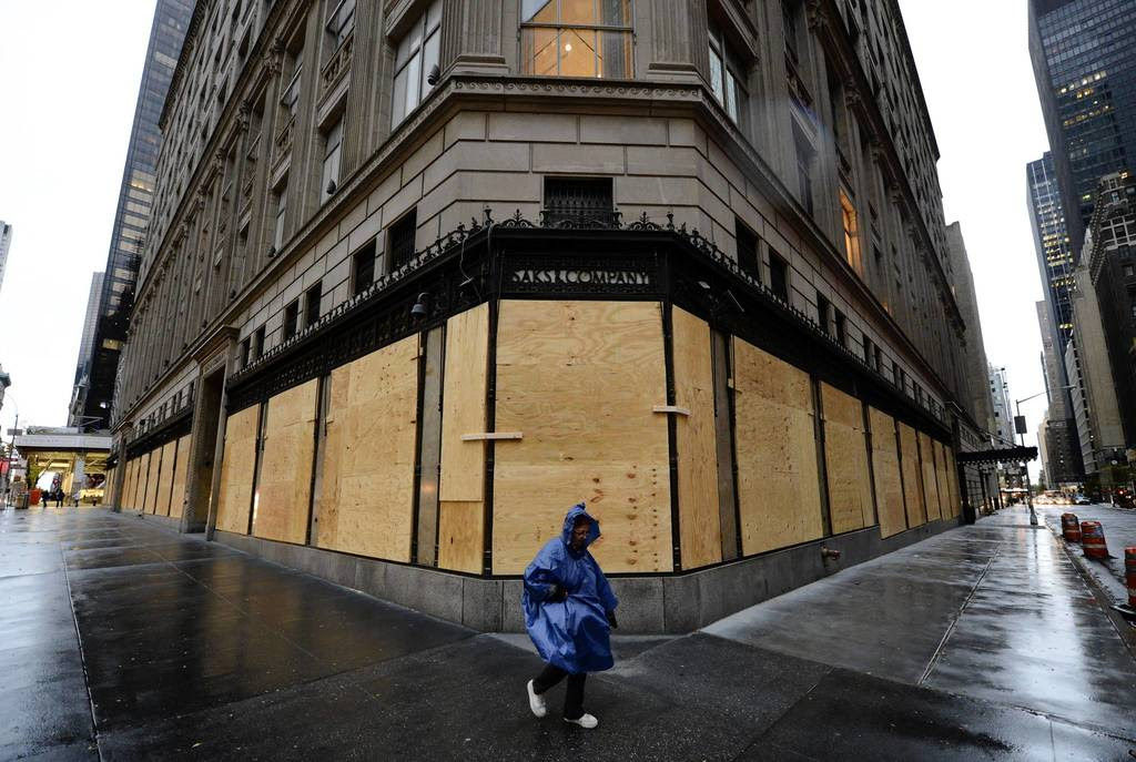 A woman walks past a boarded up Saks Fifth Avenue as New Yorkers prepare for Hurricane Sandy which is suppose to hit the city later tonight. Much of the eastern United States was in lockdown mode, awaiting the arrival of a hurricane dubbed