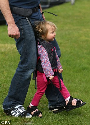 The harness attaches around an adult's waist to hold the child upright