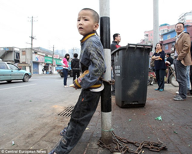 Slave auction: Fai, 8, pictured chained to a lamp post by his  father Yong Tsui, who tried to sell him to strangers in China