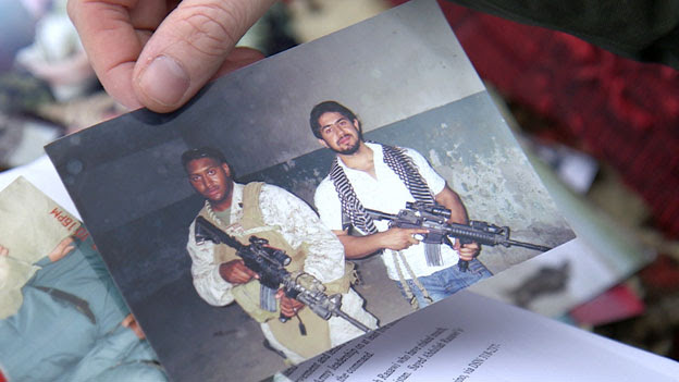A photograph showing Sayid holding a US rifle