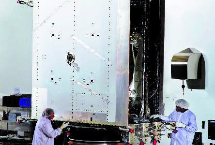 This April 9, 2015 photo provided by Lockheed Martin shows the first GPS III satellite being built in a clean room at Lockheed Martin's complex south of Denver. The satellite is scheduled to be launched from Cape Canaveral, Fla., on Tuesday, Dec. 18, 2018. (Pat Corkery/Lockheed Martin VIA AP)